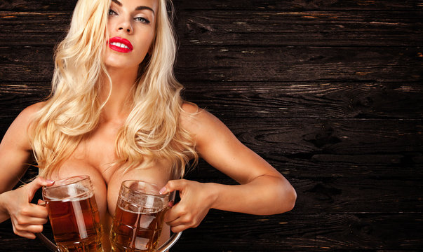 Oktoberfest Beer fest. Young sexy and naked woman, serving big mugs on wood background.