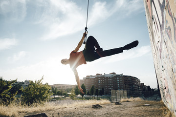 Dancer performing aerial dance on urban scenery at sunset