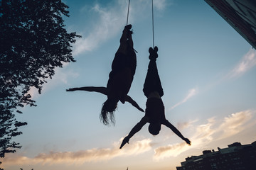 Silhouette of couple of aerial dancers performing a choreography on urban scenery at sunset