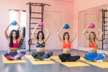 Group og young attractive women doing pair exercises with fit balls