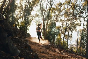 Fototapeta Woman trail running on a mountain path obraz