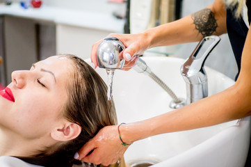 Washing the head of the client in a hairdresser's shampoo, before the hair restoration procedure, botox hair