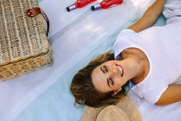 Top view of a smiling woman lying outdoors with eyes closed