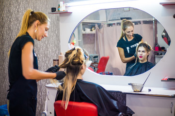 The hairdresser applies nutritious and healing components to damaged hair, applying botox to the hair, combs every strand