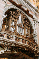 Church in Naples, frescoes and stucco work inside. Beautiful decoration and historical vaults. Symmetry and paintings under the dome. The organ is gilded, the altar, and the icons on the walls.