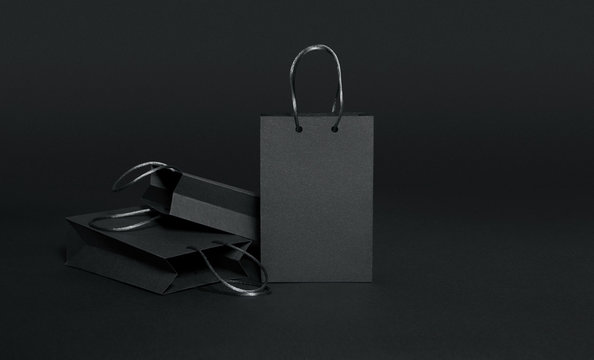 Black shopping bags on black background, black friday sale template