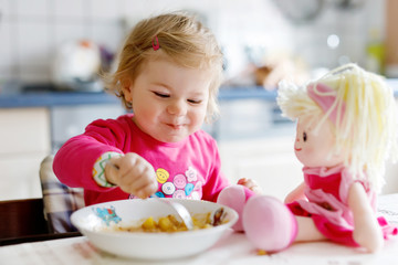 Adorable baby girl eating from fork vegetables and pasta. Little child feeding and playing with toy doll. Cute toddler, daughter with spoon sitting in highchair and learning to eat by itself.