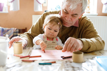 Cute little baby toddler girl and handsome senior grandfather painting with colorful pencils at home. Grandchild and man having fun together. Family and generation in love