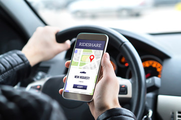 Ride share driver in car using the rideshare app in mobile phone. New taxi ride request from customer in smartphone application. Man picking up passengers for online carpool service.
