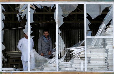 Afghan men look outside a broken window at the site of a suicide attack in Kabul