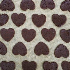 Uncooked heart shaped cookies, raw dough and heart shaped cookie cutter. top view. Square image.