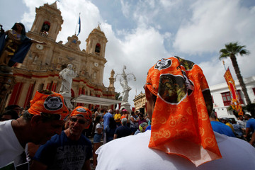 Cyclists wear bandanas with holy pictures at the end of the annual bicycle and motorcycle pilgrimage outside the Parish Church and Sanctuary of Our Lady of Graces during the village feast in Zabbar