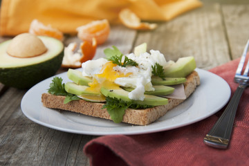 Bread toasts with avocado, eggs and greens. Tasty breakfast. Wood background. Isoalted.