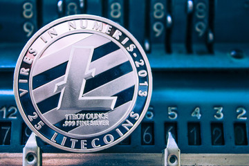 Coin of litecoin on the background of numbers adding machine.