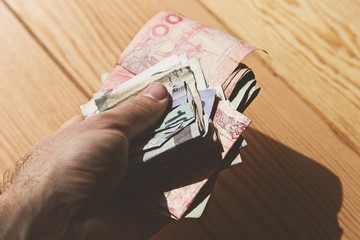 A hand holding cash from various countries. This image can be used to represent global currency.