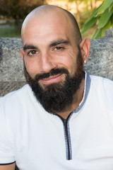 Outdoor portrait of smiling young bald beard man