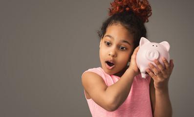 Cute little black girl holding piggy bank
