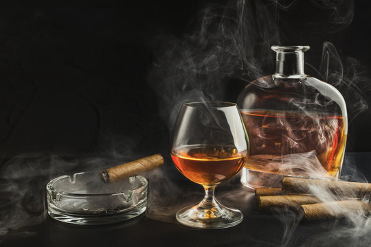 Glass of whiskey with smoking cigar and bottle
