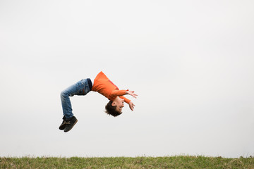 Foto auf Acrylglas Gymnastik healthy sport little boy jumping somersault outdoors nature with copyspace