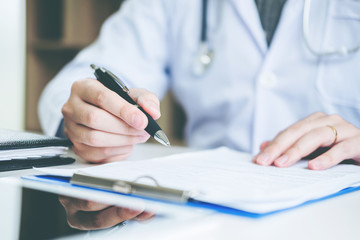 Doctor typing information working in Hospital office focus on Stethoscope