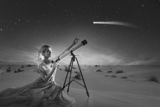 Young woman dreams, concept. Girl looks at a comet or falling star uses a telescope.  Desert background,