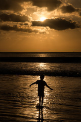 A single child playing in the ocean at sunset