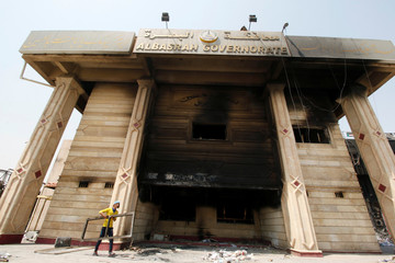 A man cleans the building of Basra Governorate after demonstrations during which protesters torched the Basra Governorate in Basra