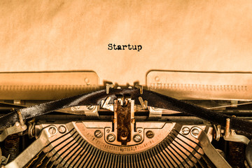 the word Startup printed on a piece of paper by a typewriter. retro objects.