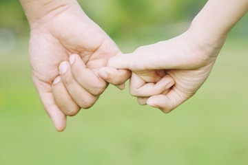 Loving Young love Woman and man  holding hand Shake hand together, couple be hand in hand pinky promise or pinky swear. Happy romantic love in the garden. concept couple lover valentine day.
