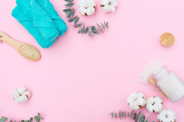 Beauty background with towels, green leaves and cotton buds on pink background with copy space