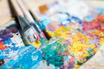 Bunch of paintbrushes in paints over palette with mixed colors such as yellow, blue and others