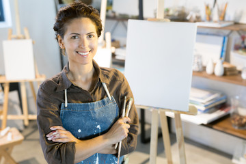 Smiling young woman in apron holding paintbrushes while crossing her arms on chest in studio