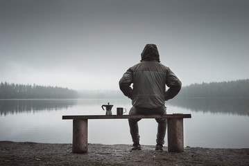 A man is sitting on a bench and looking at the lake. Back view. Also a coffee maker and a mug on the bench.