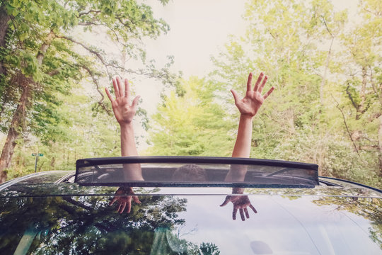 Boy putting his  hands out of the car sunroof top, driving down a country road
