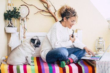 beutiful caucasian woman and funny old pug dog sitting on a bench in the terrace at home working or doing onine shopping with a laptop together. friendship and alternative office location concept