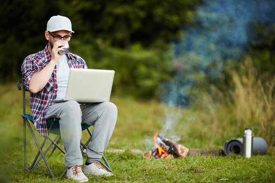 Young modern backpacker with laptop drinking tea by campfire and browsing in the net