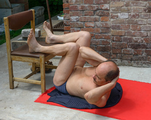 Man is doing abdominal crunches in his backyard.