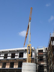 A yellow construction crane working on a modern concrete apartment development with scaffolding with blue sky and sunlight