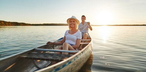 Smiling young couple canoeing together on a lake in summer Wall mural
