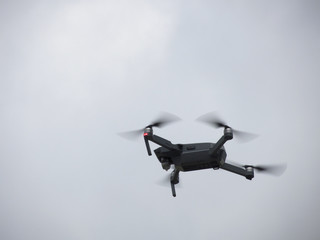 Quadcopter drone flying overhead in cloudy sky