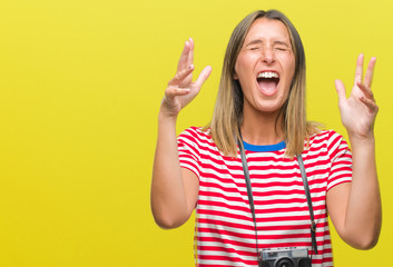Young beautiful woman taking pictures using vintage photo camera over isolated background crazy and mad shouting and yelling with aggressive expression and arms raised. Frustration concept.
