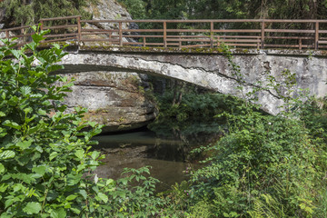 Stone bridge over the river. Bohemian switzerland. Rocks above the river. Rocky valley.