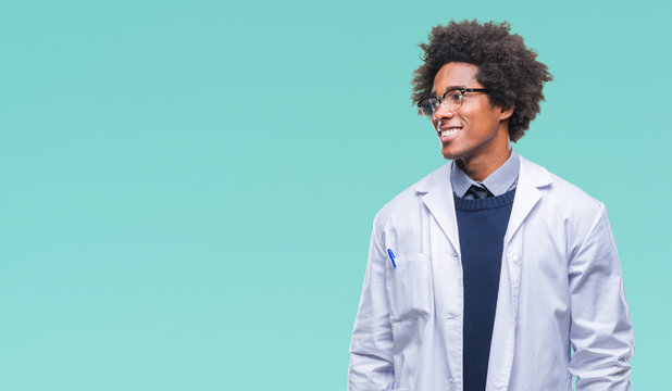 Afro american doctor scientist man over isolated background looking away to side with smile on face, natural expression. Laughing confident.