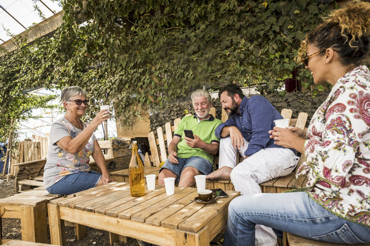 caucasian family in relationship and friendship sitting outdoor in a natural place made with recycled wood. from grandfthers to mother to son. old, middle age and teenager all together enjoying
