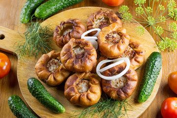 Fried meat pies belyash with vegetables on wooden board