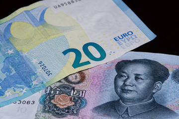 Twenty euro banknote is above ten chinese yuan on black background