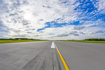Airport runway to in horizon and picturesque clouds in the blue sky.