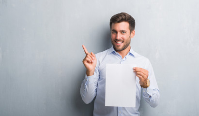 Handsome young man over grey grunge wall holding blank paper sheet contract very happy pointing with hand and finger to the side