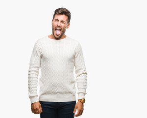 Young handsome man wearing winter sweater over isolated background sticking tongue out happy with funny expression. Emotion concept.