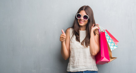 Young brunette woman over grunge grey wall holding colorful shopping bags happy with big smile doing ok sign, thumb up with fingers, excellent sign